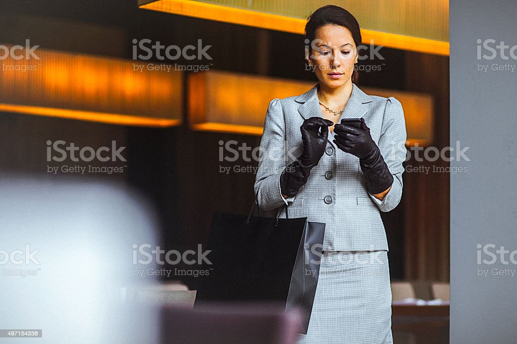 Beautiful, elegant woman using mobile phone at cafe stock photo