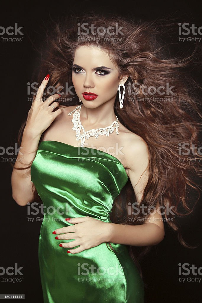 Beautiful elegant woman with long curly hairs in green dress royalty-free stock photo
