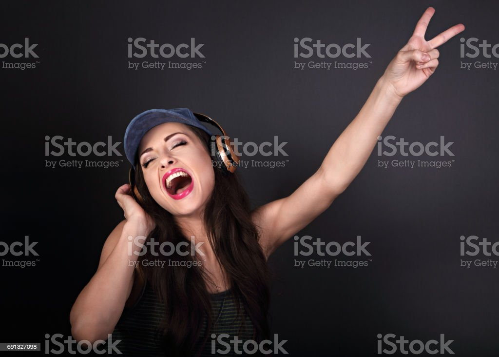 Beautiful emotional dancing and singing woman in blue cap listening the music in wireless headphone and hand showing v sign on dark grey background stock photo
