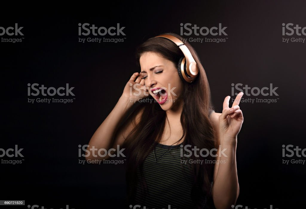 Beautiful emotional loudly singing woman listening the music in wireless headphone and hand showing v sign on dark background stock photo