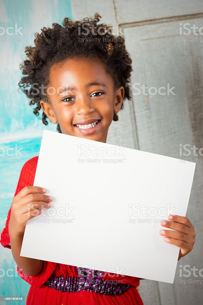 Beautiful Ethiopian child smiling while holding blank sign stock photo