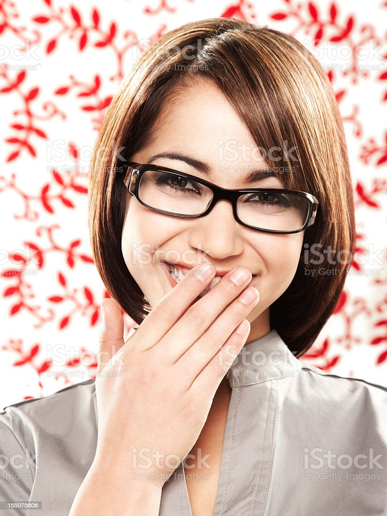 Beautiful ethnic woman in glasses covering her mouth while laughing royalty-free stock photo