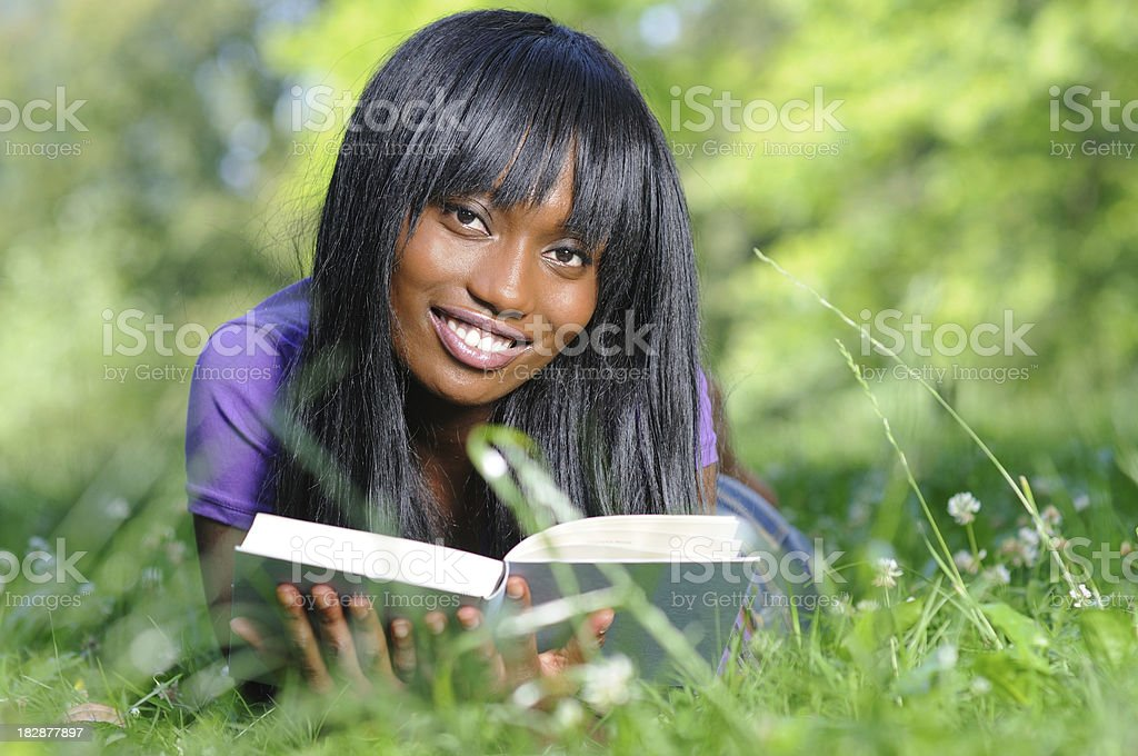 Beautiful ethnic woman reading a book in park royalty-free stock photo