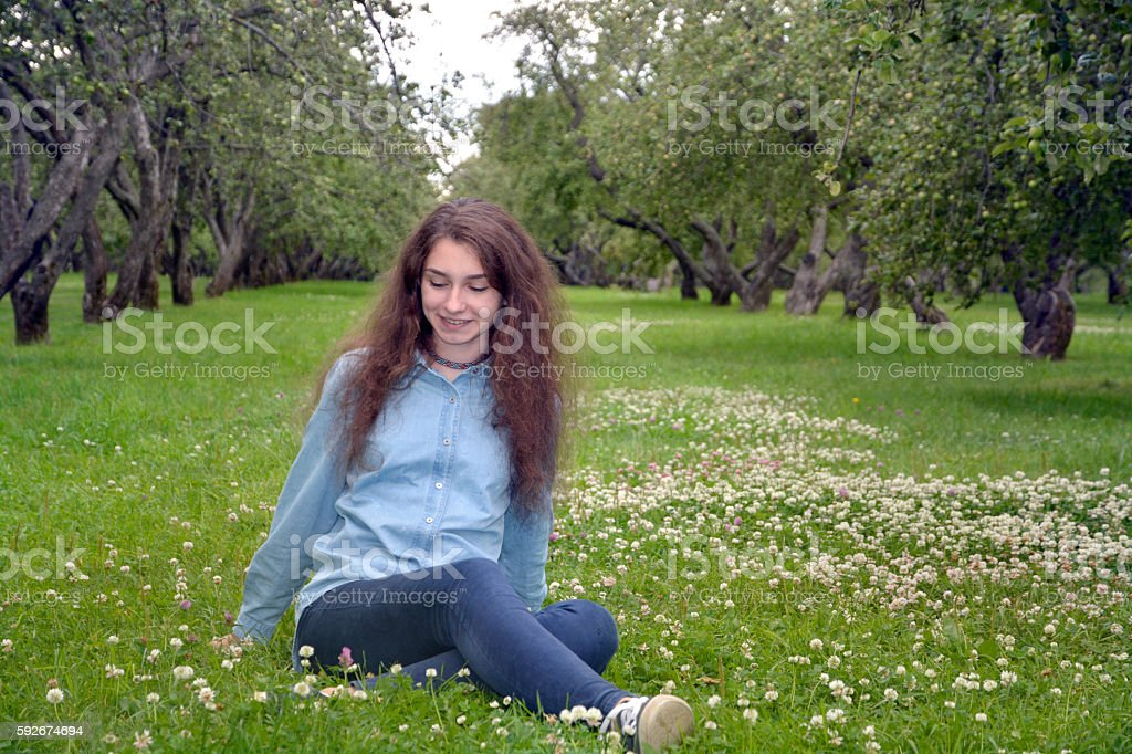 beautiful european girl sitting on a green meadow stock photo