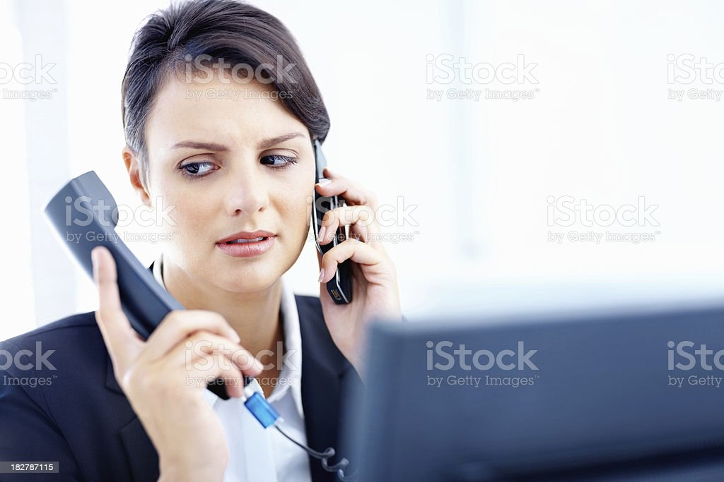 Beautiful executive holding telephone handset and cellphone royalty-free stock photo