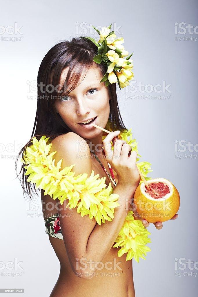 Beautiful exotic girl with Hawaiian accessories drinking grapefruit juice stock photo
