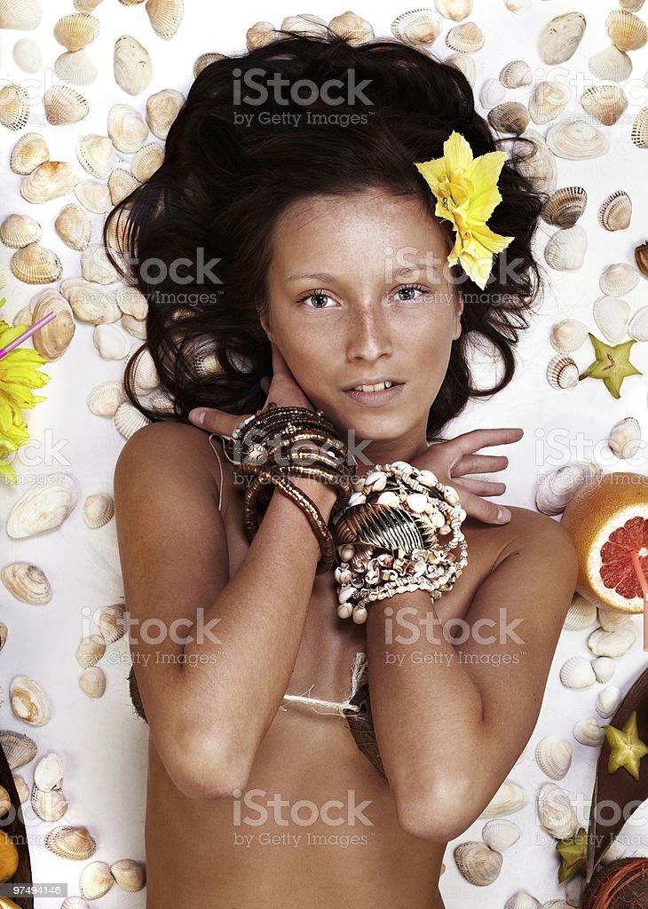 Beautiful exotic girl with Hawaiian accessories lying royalty-free stock photo