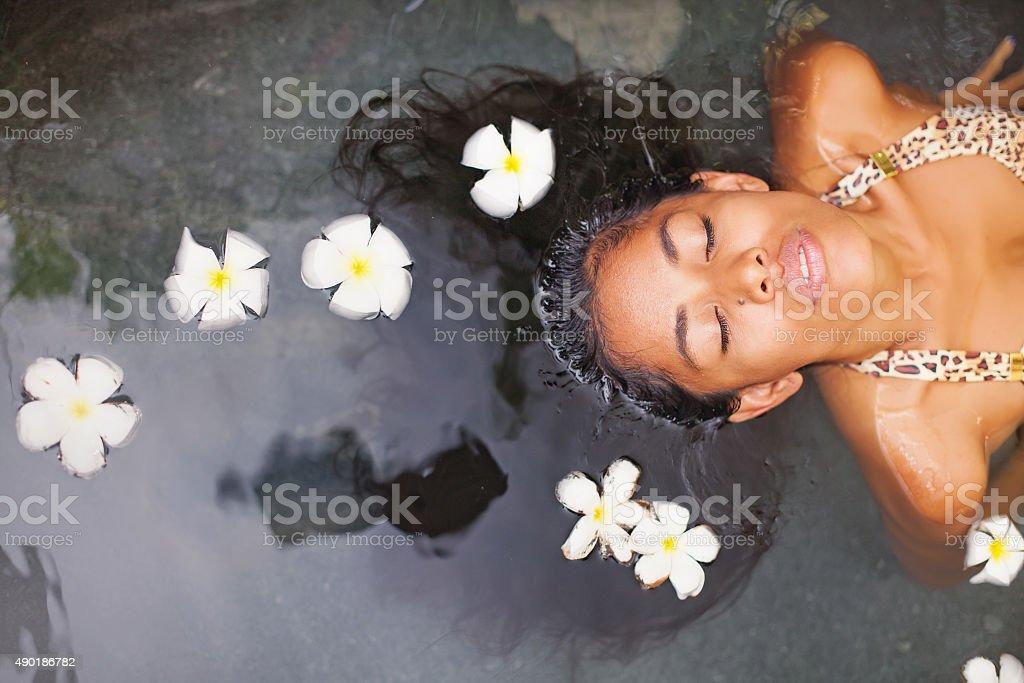 Beautiful exotic woman having bath in a luxury spa salon stock photo