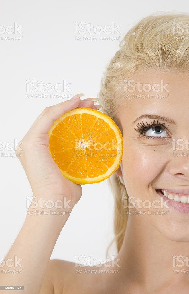 beautiful face of blond model with orange sliced in half royalty-free stock photo
