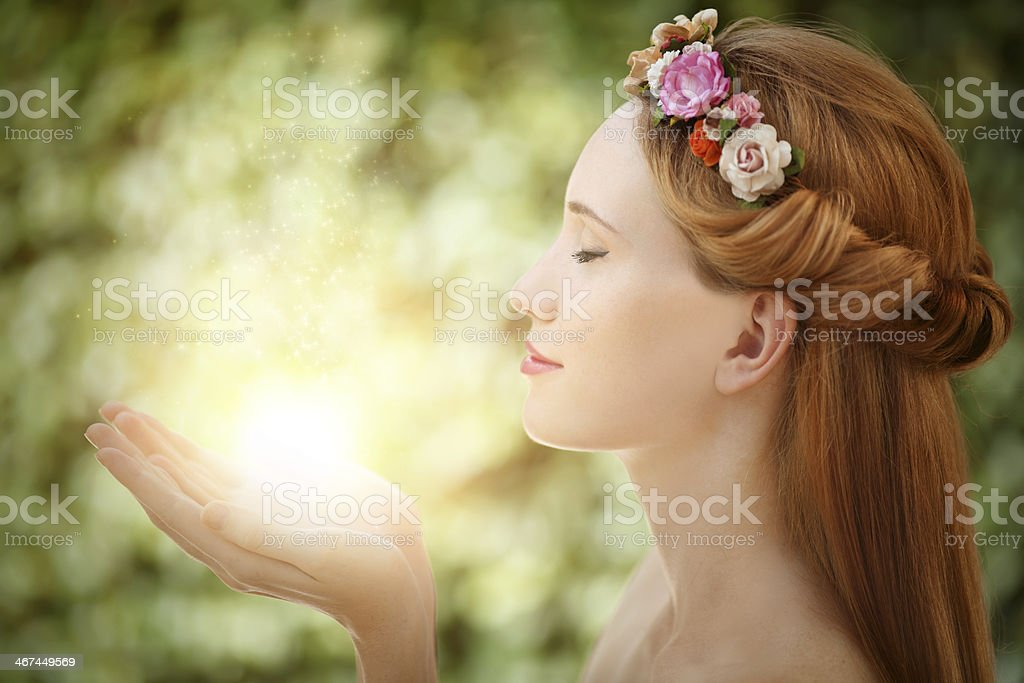 Beautiful fairy woman with glow in hands on green background stock photo