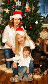 Beautiful family in Santa red hats near Christmas tree