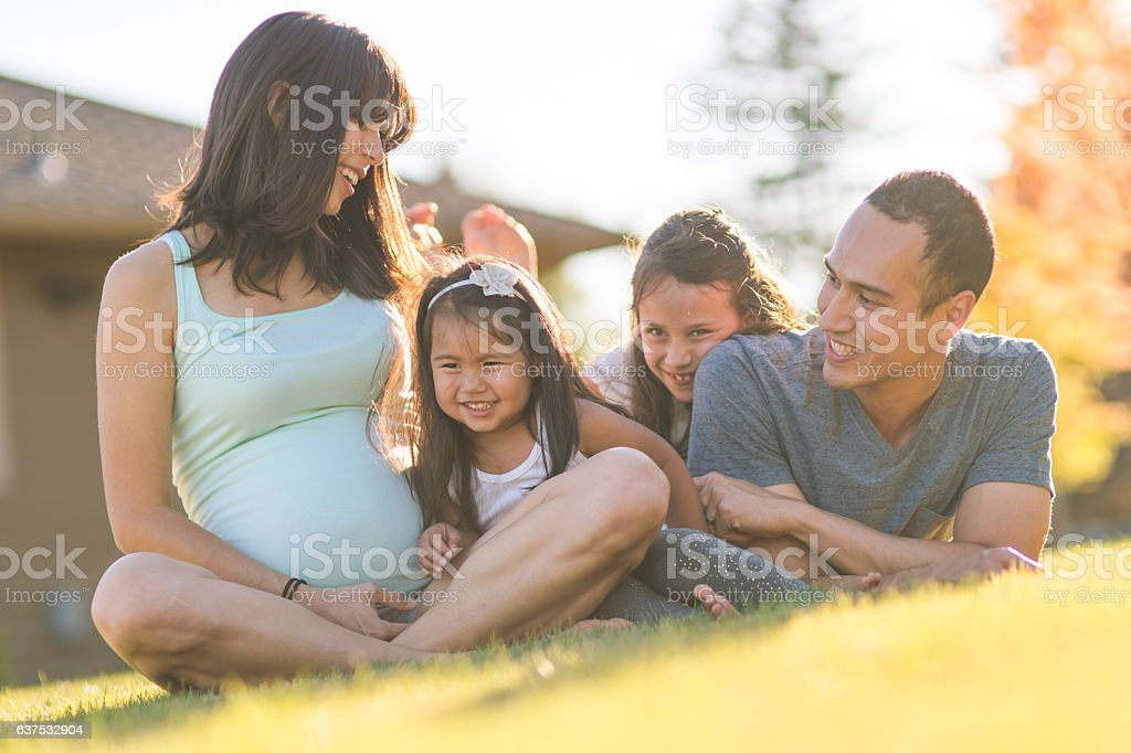 A beautiful ethnic family of four is playing and spending stock photo