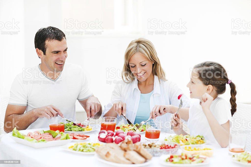 Beautiful family of three enjoying in the dinner. royalty-free stock photo