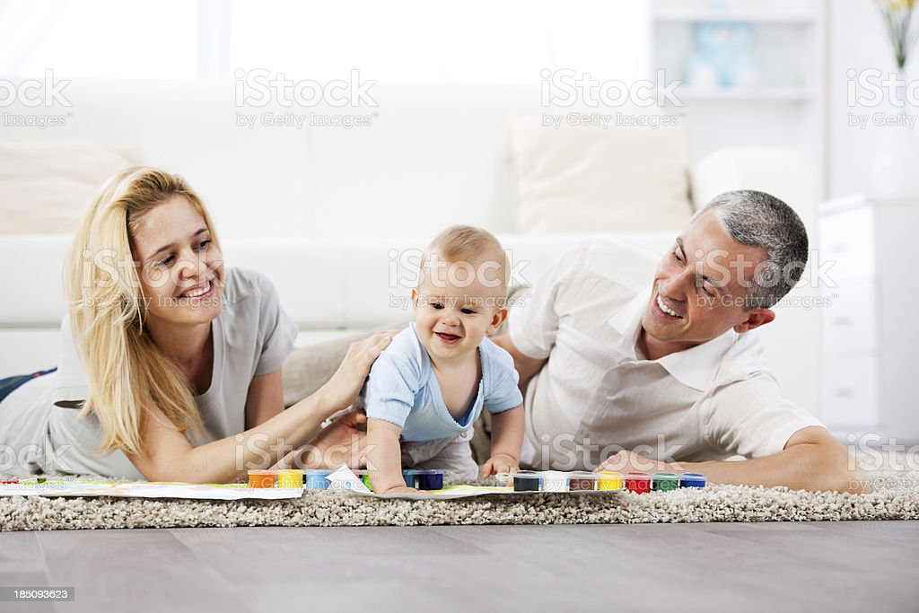 Beautiful family of three people painting with watercolors royalty-free stock photo