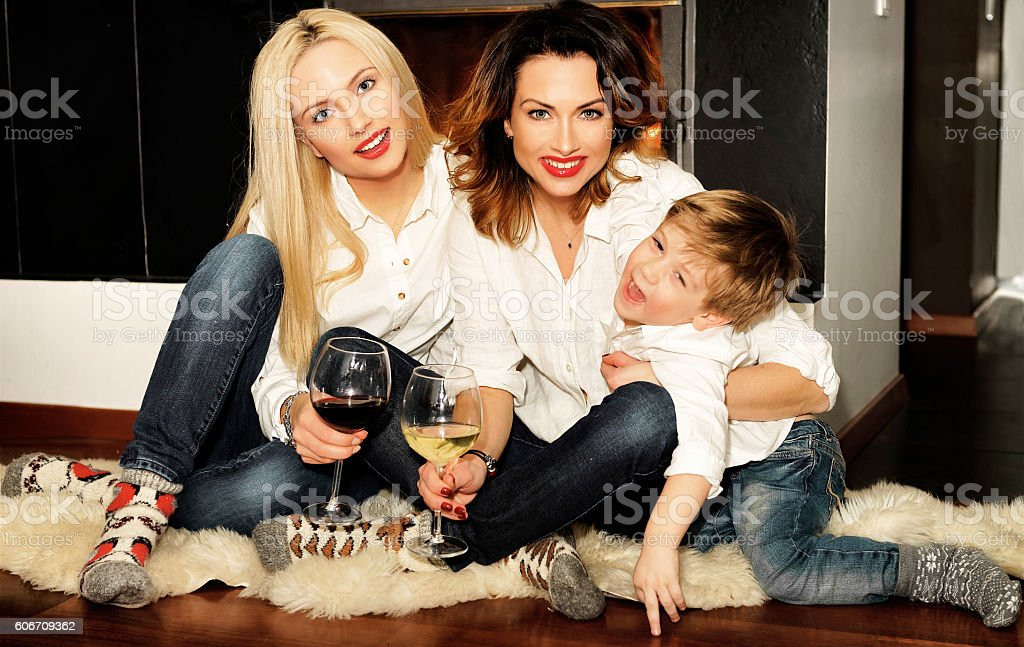 Beautiful family sitting at the fireplace stock photo