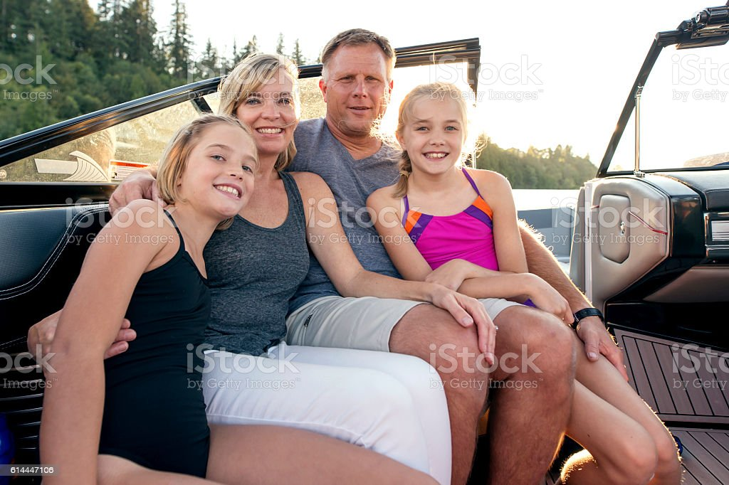 Beautiful family sitting inside  a ski boat and smiling stock photo