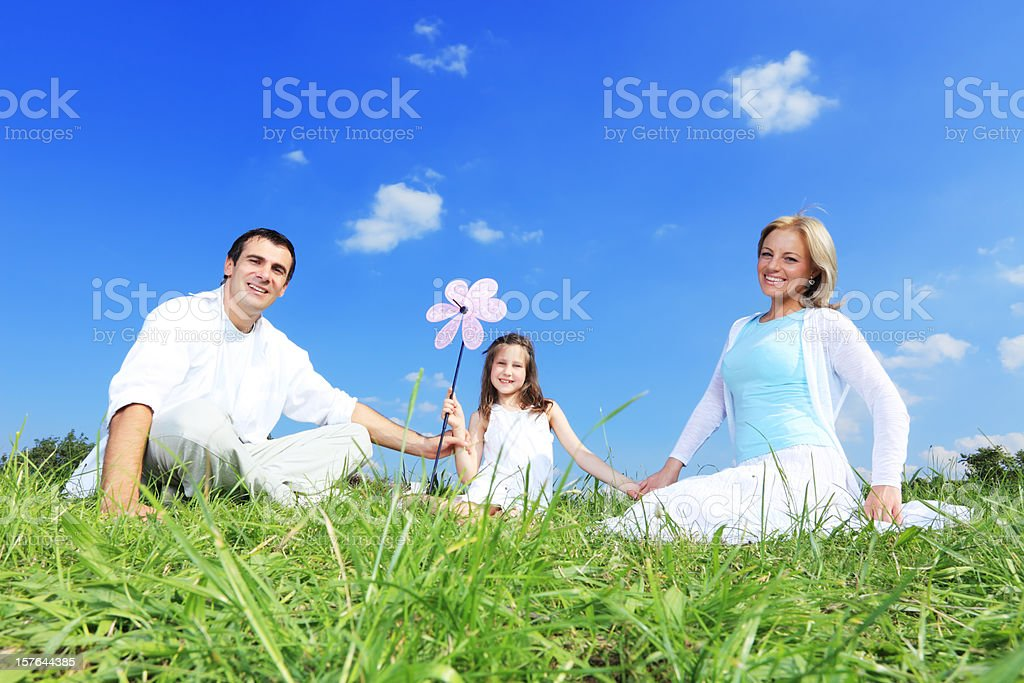 Beautiful family sitting on the grass and looking at camera royalty-free stock photo