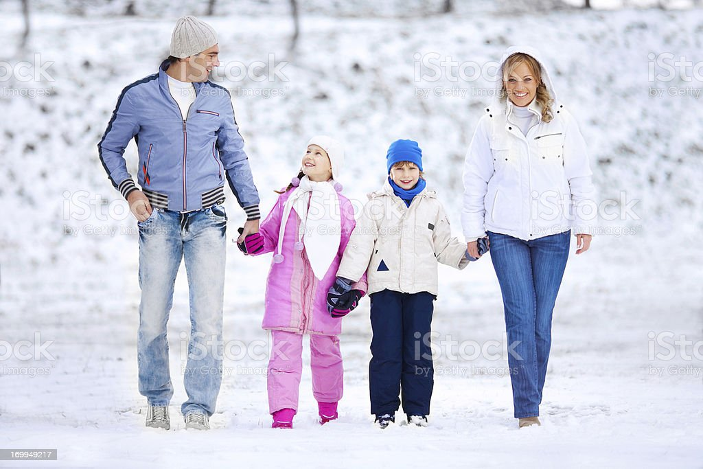 Beautiful family walking in park during winter. royalty-free stock photo