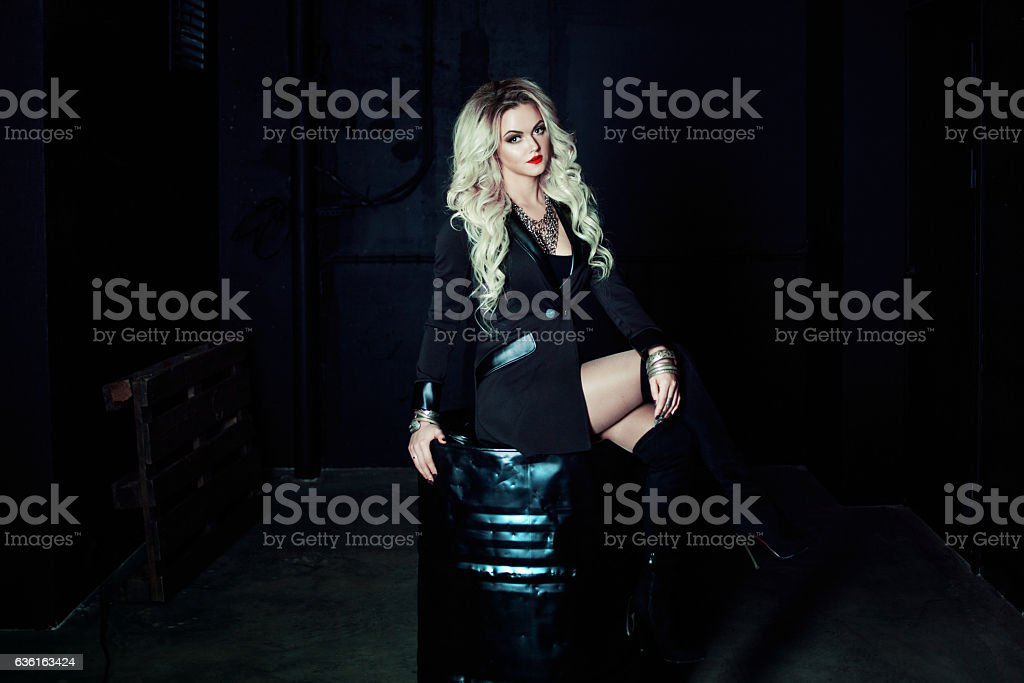 Beautiful fashion blonde woman in black sitting on a metal stock photo
