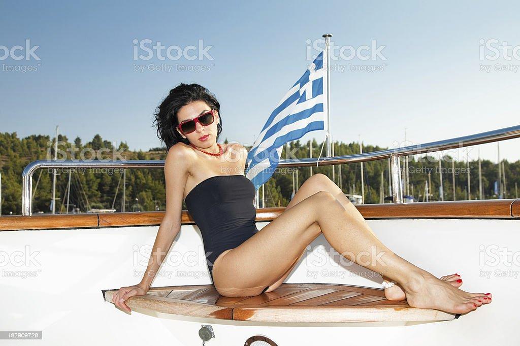 Beautiful fashion model sunbathing and posing on luxury yacht royalty-free stock photo