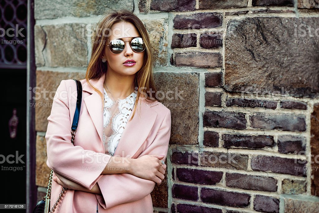 Beautiful fashion model woman on sunglasses standing near brick wall stock photo