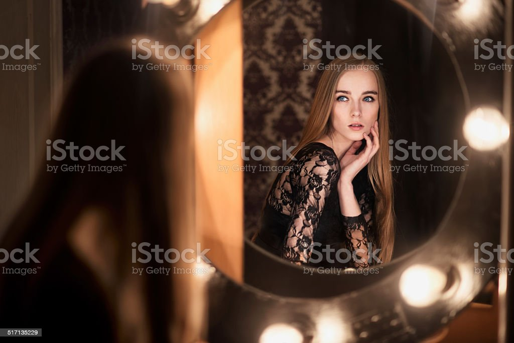 Beautiful fashion model woman posing near the mirror stock photo