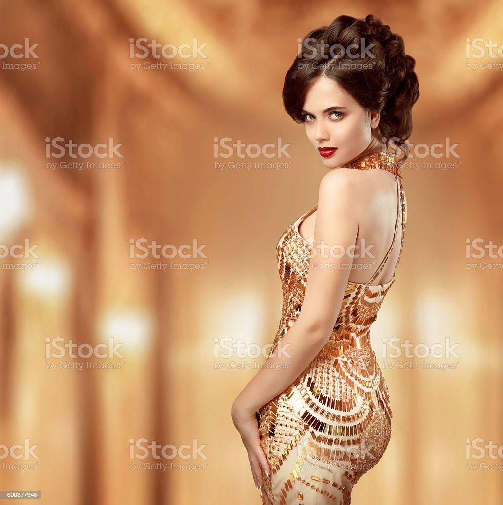 Beautiful fashion woman in gold dress, elegant lady stock photo