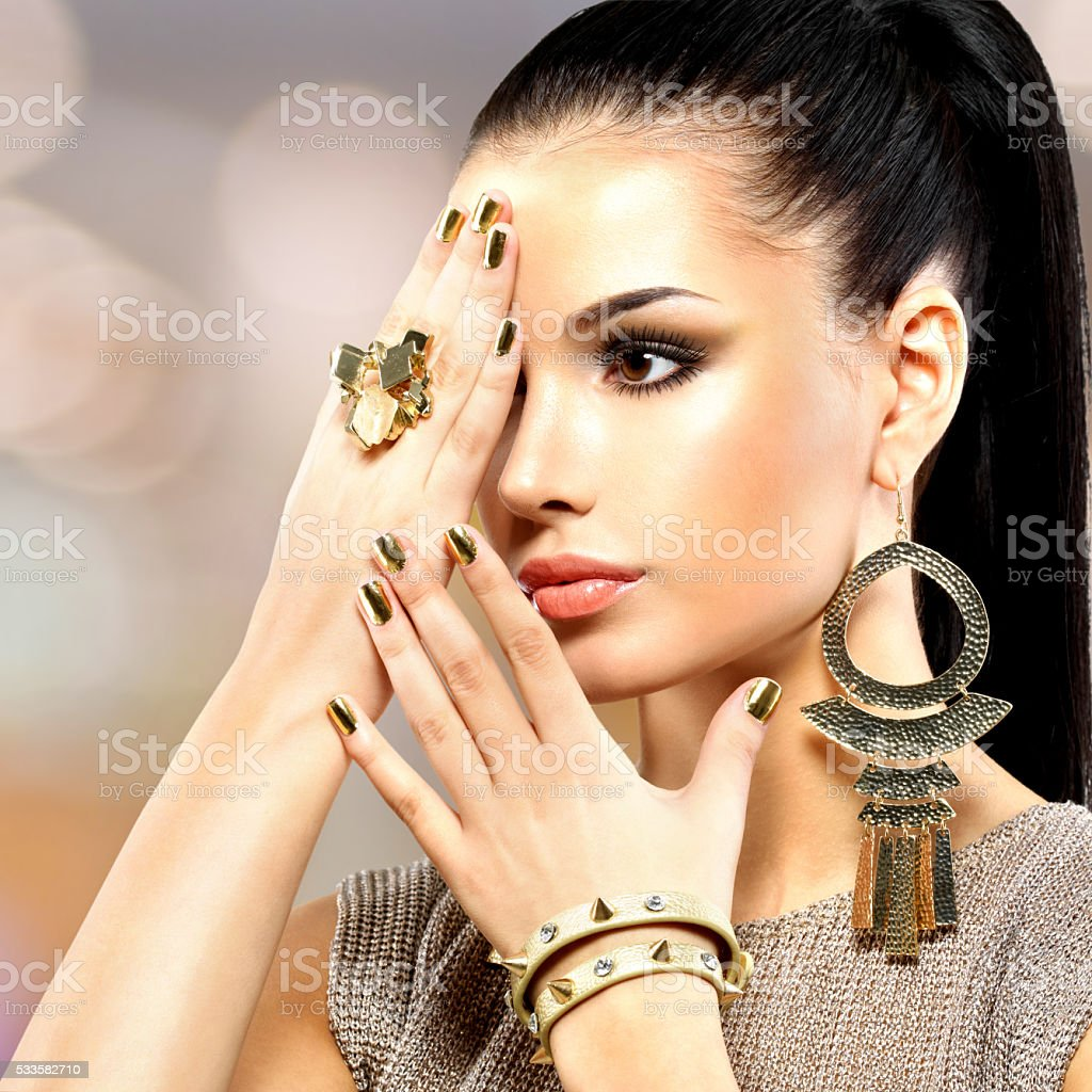 Beautiful fashion woman with black makeup and golden manicure stock photo