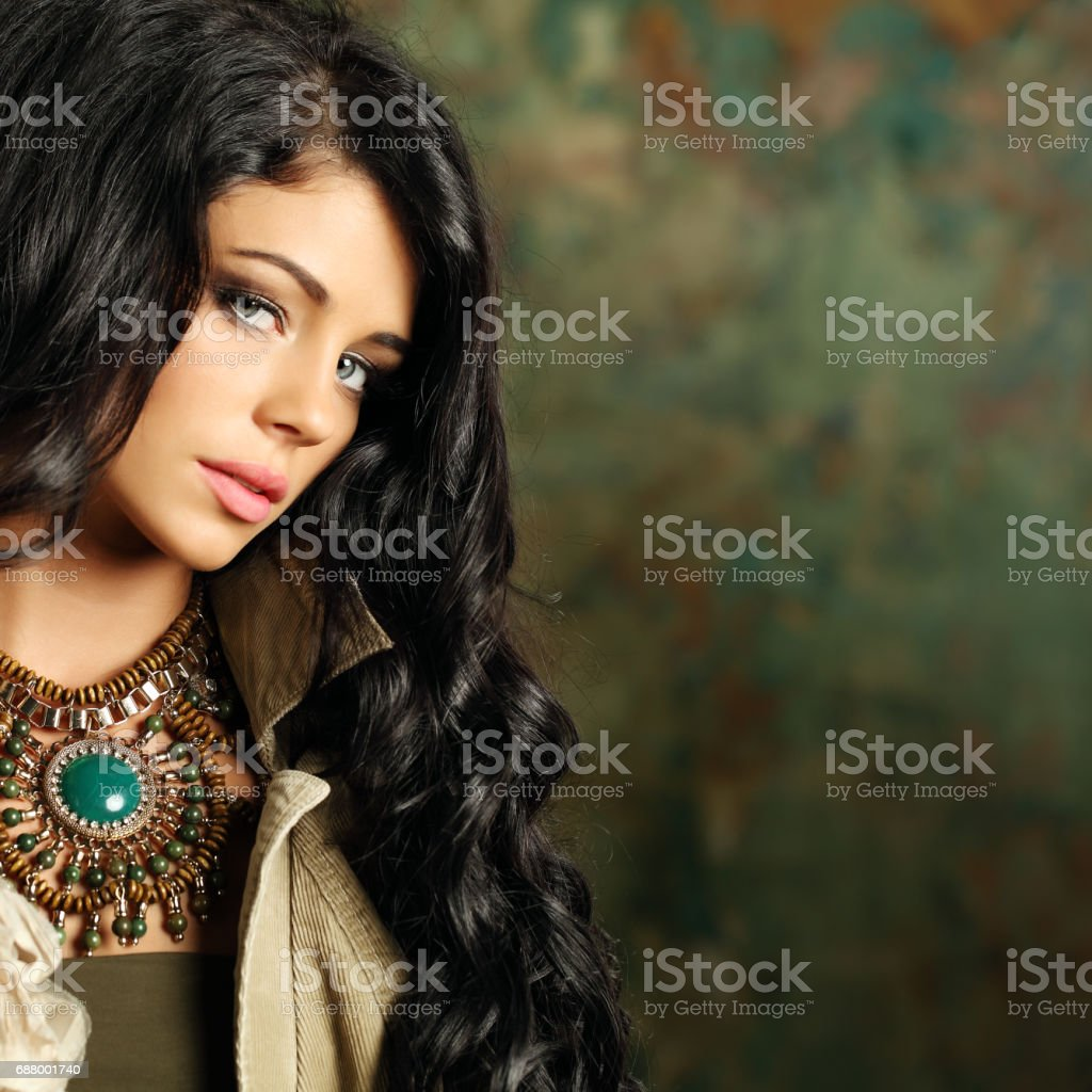 Beautiful fashion woman with curly hair and stage makeup on background stock photo