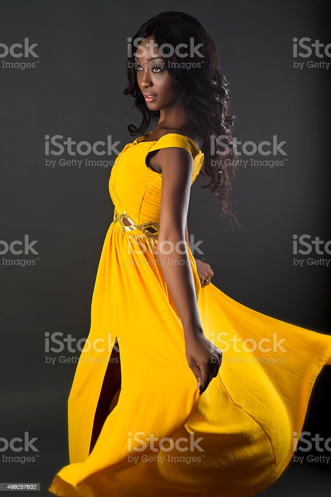 Beautiful fasion model posing in yellow gown stock photo