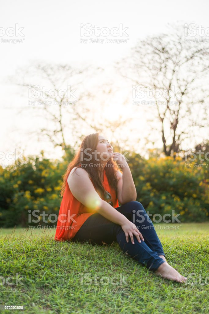 Beautiful fat woman relax fashion in the green park stock photo
