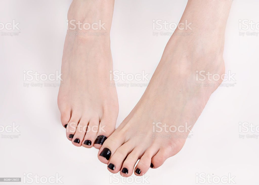 Beautiful feet with black lacquer on the nails stock photo