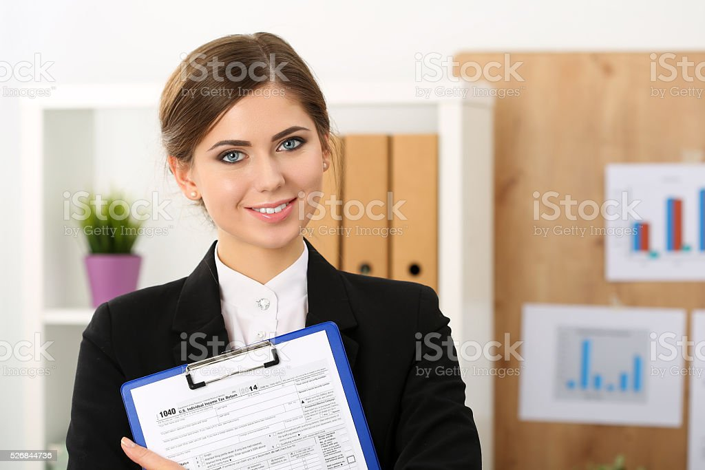 Beautiful female accountant hold income tax return form stock photo