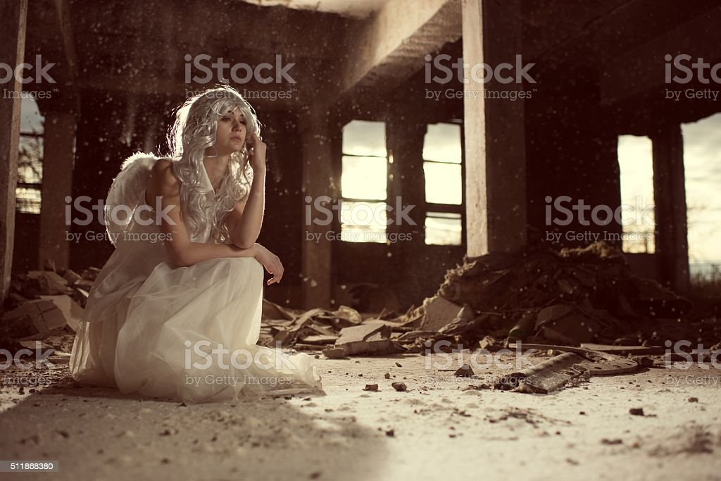 Beautiful female angel in an old ruin. stock photo