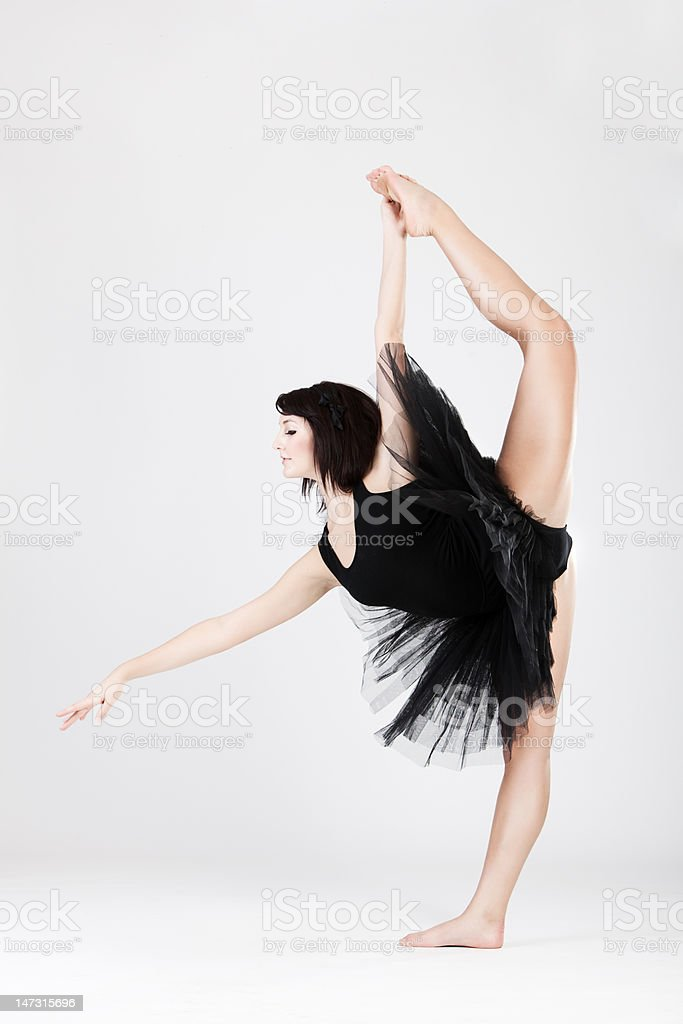 Beautiful female ballerina doing split against white royalty-free stock photo