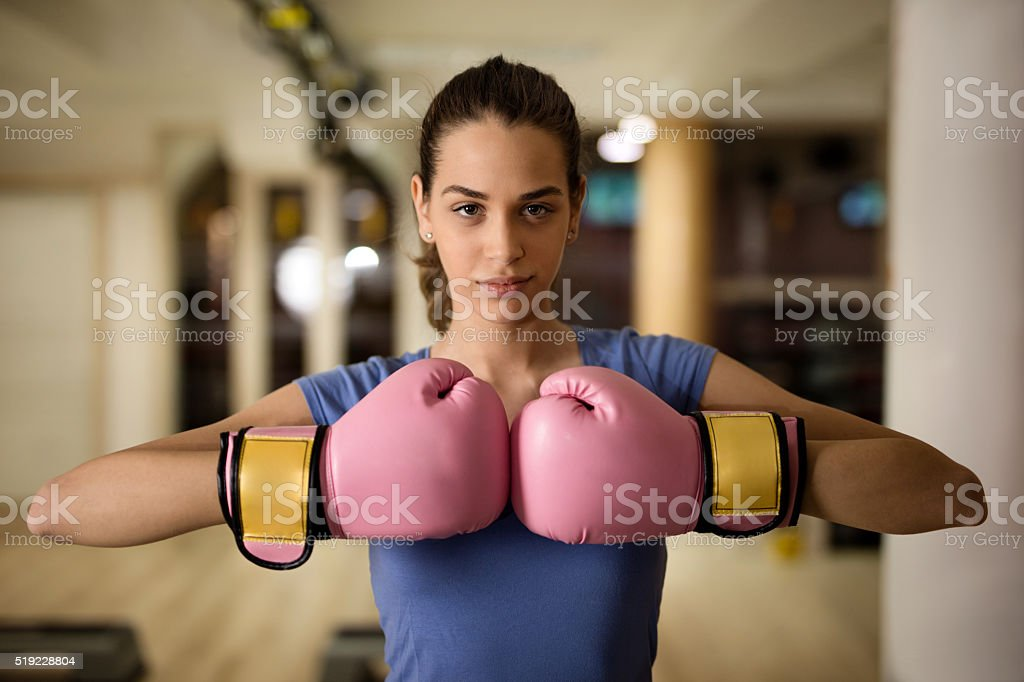 Beautiful female boxer in a fighting stance at health club. stock photo