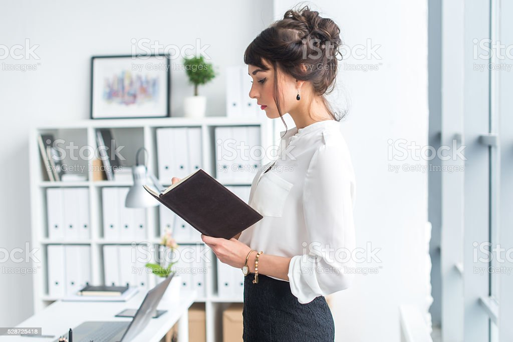 Beautiful female clerk standing in office at her workplace, holding stock photo