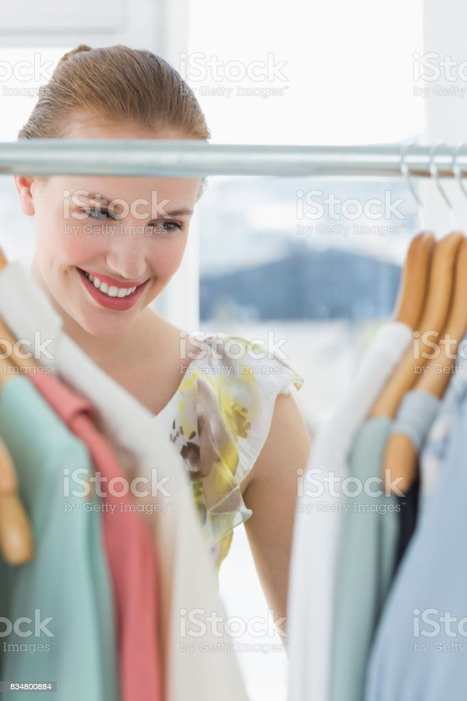 Beautiful female customer selecting clothes at store stock photo