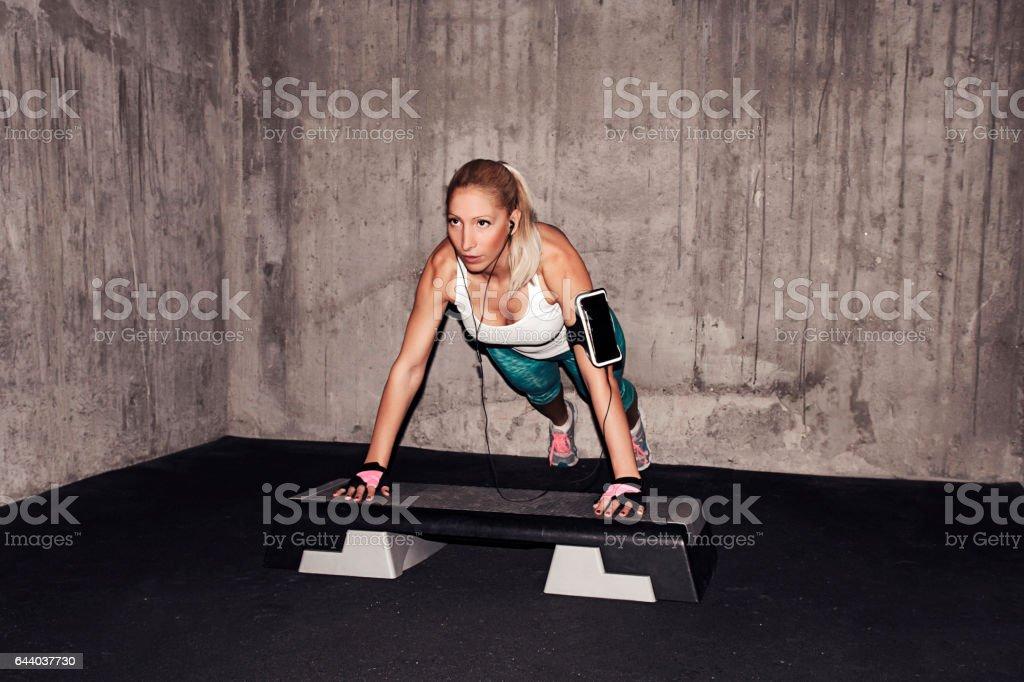 Beautiful female doing push-ups on the step board stock photo