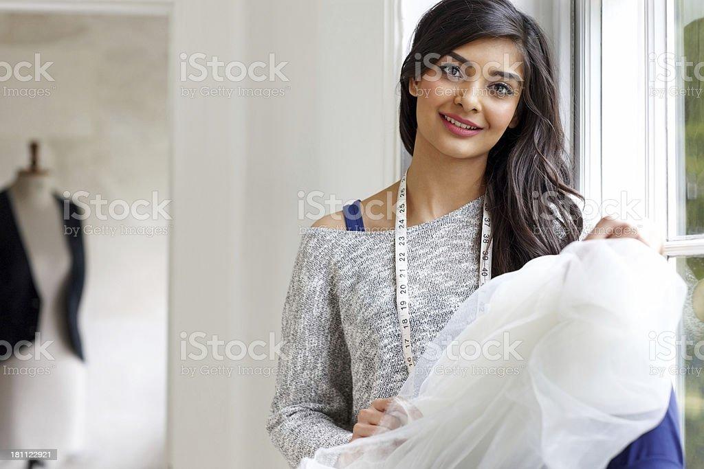 Beautiful female dressmaker at her workshop royalty-free stock photo