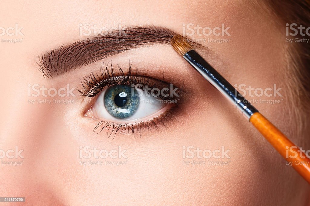 Beautiful female eyes with make-up and brush stock photo