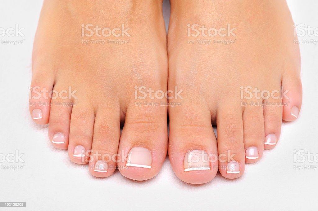 Beautiful female feet with French pedicure closeup stock photo