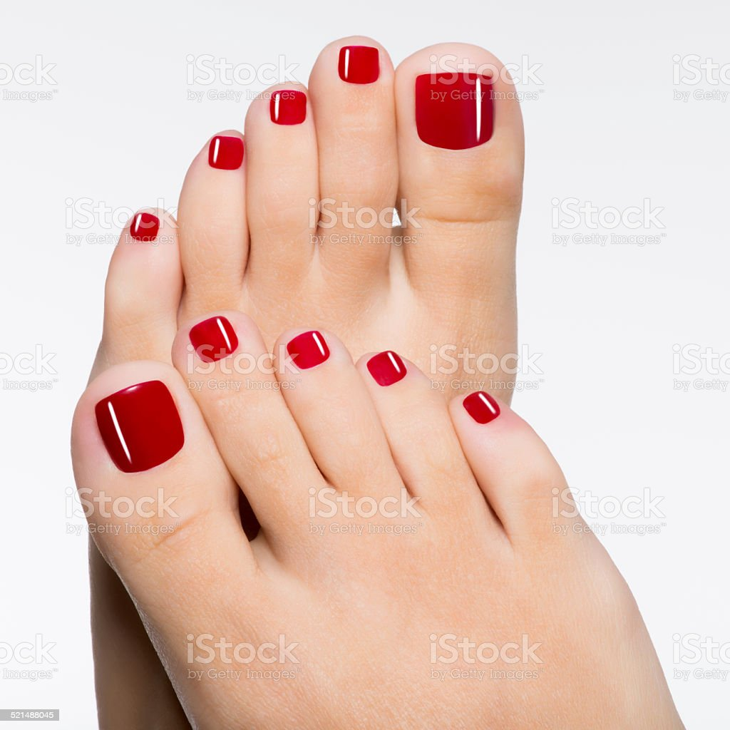 Beautiful female feet with red pedicure stock photo