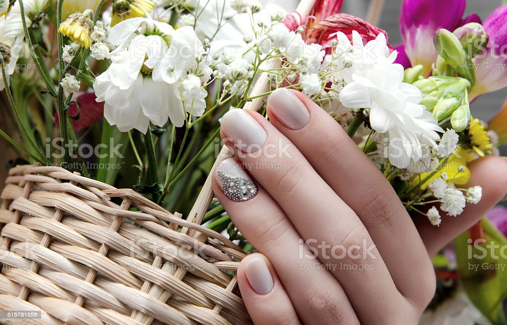 Beautiful female hand with beige nail design stock photo