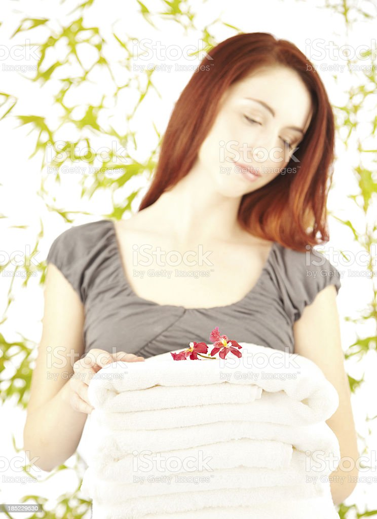 Beautiful female holding a pile of white towels royalty-free stock photo