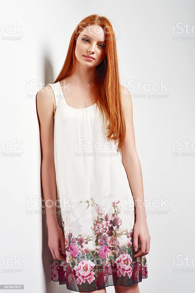 Beautiful female in sleeveless flower print summer dress stock photo