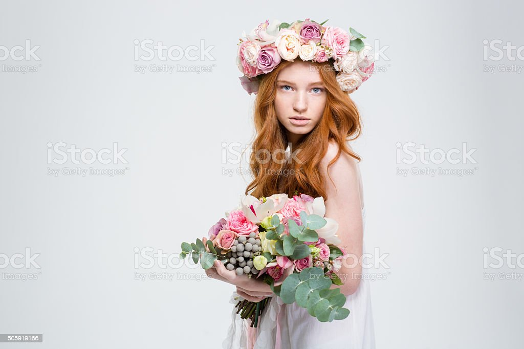 Beautiful female in wreath of roses posing with flower bouquet stock photo