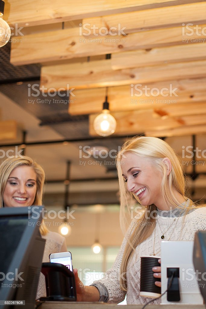 Beautiful female is so excited to pay with her smartphone stock photo