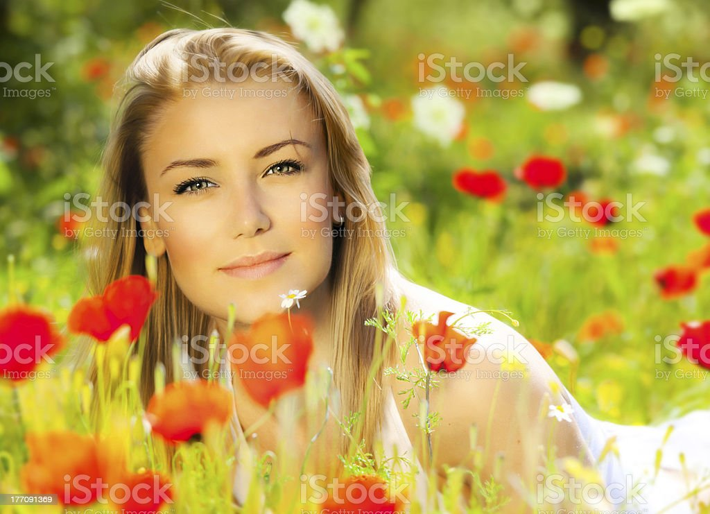 Beautiful female laying on the flower field royalty-free stock photo