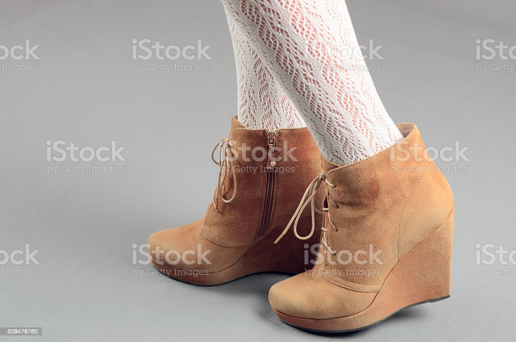 Beautiful female legs in brown suede boots stock photo